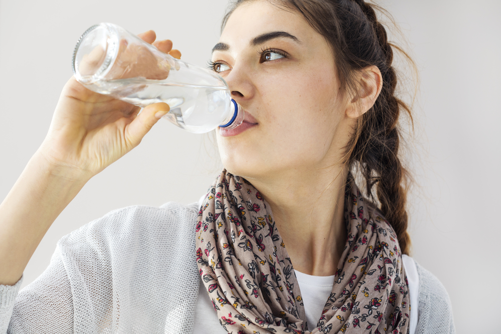 A woman drinking from a bottle of water.