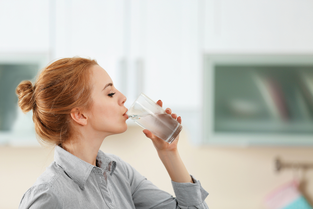 A red-headed woman drinking water.