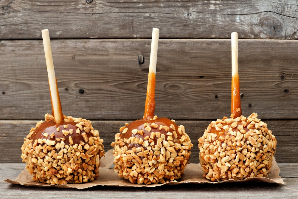 Three caramel apples covered in nuts.