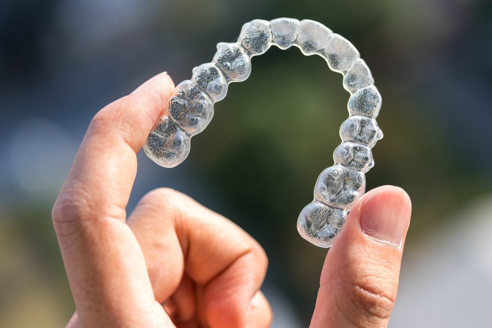 Holding an invisible orthodontic retainer.