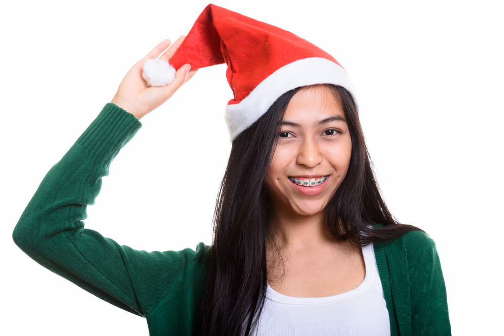 A teenager with braces wearing a santa hat.