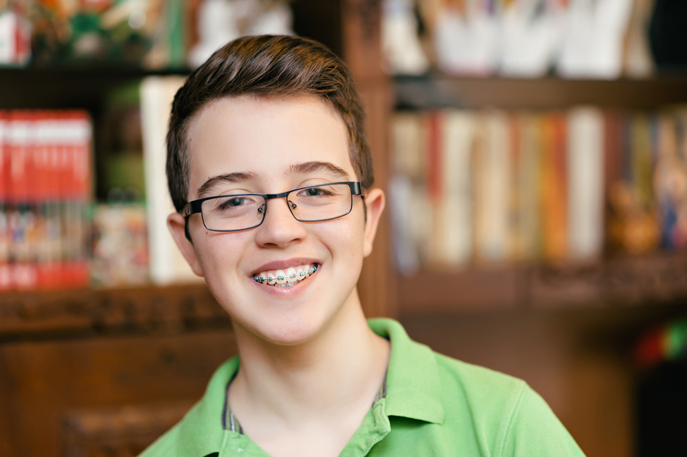 A teen boy with glasses and braces smiling.