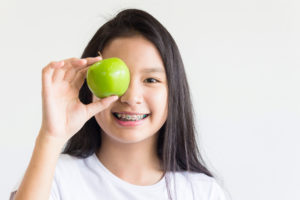 A smiling young girl with braces holding a green apple up to her eye.