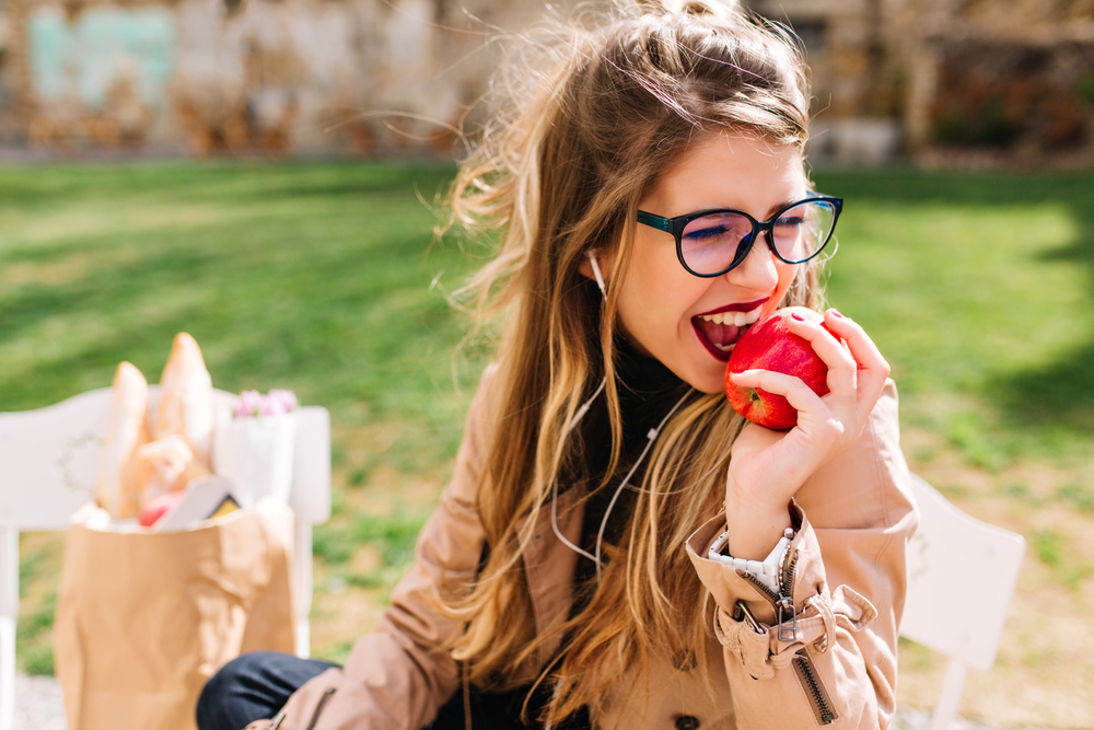A woman with glasses biting into a whole apple.