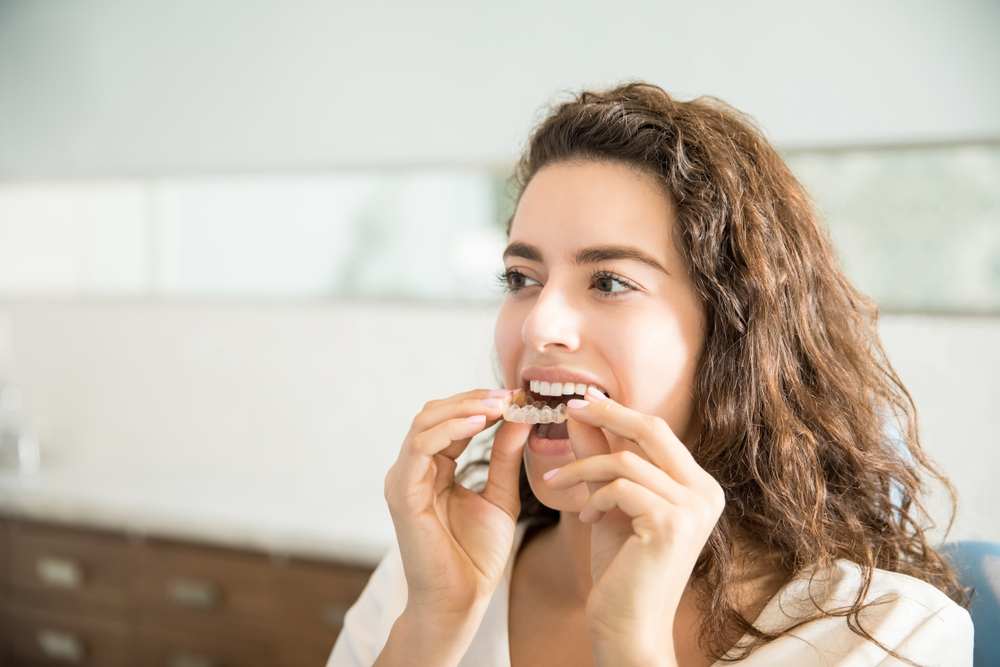 A woman putting in an Invisalign aligner.